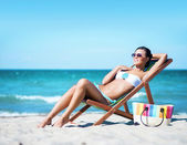 Sexy woman lying on deckchair — Stock Photo