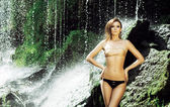 Woman in swimsuit near waterfall — Stock Photo