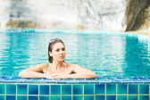 Woman relaxing in pool at summer — Stock Photo