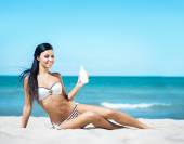 Woman using  suntan cream on beach — Stock Photo
