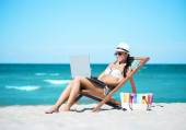 Woman with laptop relaxing on beach — Stock Photo