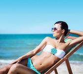 Woman relaxing on deckchair on beach — Stock Photo