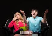Family watching sport broadcast on laser projector — Stock Photo