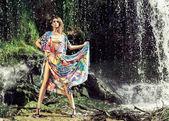 Woman posing in dress near waterfall — Stock Photo