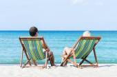 Man and woman chilling in deckchairs — Stock Photo