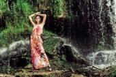 Mujer en vestido posando frente a cascada — Foto de Stock