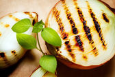 Grilled onion served with fresh basil — Stock Photo
