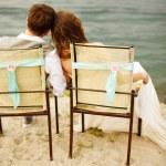Newlyweds couple sitting near water on the beach — Stock Photo #67640001