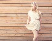 Outdoor summer sensual fashion portrait beautiful young blond woman lifts the edge of a white dress standing on the background of wooden planks. Toned in warm colors — Foto de Stock