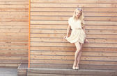Outdoor summer sensual fashion portrait beautiful young blond woman lifts the edge of a white dress standing on the background of wooden planks. Toned in warm colors — Stock Photo