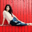 Beautiful tall girl with long hair brunette in jeans sits near wall of red wooden planks — Stock Photo #53017161