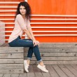 Beautiful tall girl with long hair brunette in jeans sits near wall of orange old white wooden planks — Stock Photo #53017211