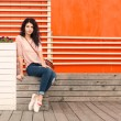 Beautiful tall girl with long hair brunette in jeans sits near wall of orange old white wooden planks — Stock Photo #53017227