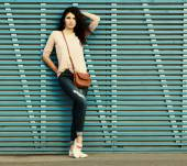 Beautiful brunette girl stands near a wall of colored wooden planks — Foto de Stock