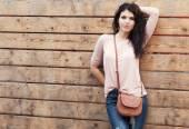 Beautiful brunette girl stands near a wall wooden planks — Стоковое фото