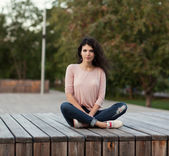 Beautiful tall girl with long hair brunette in jeans sits on wooden planks — Stock Photo