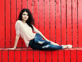 Beautiful tall girl with long hair brunette in jeans sits near wall of red wooden planks — Stock Photo