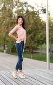 Beautiful tall girl with long hair brunette in jeans standing on old wooden planks on a warm summer evening — Foto de Stock
