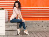 Beautiful tall girl with long hair brunette in jeans sits near wall of orange old white wooden planks — Foto de Stock