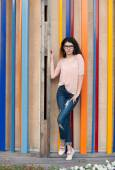 Beautiful tall girl with long hair brunette in glasses standing near colorful wall background — Foto de Stock