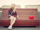 Sad lonely girl sitting on a bench near to a big red heart — Stock Photo