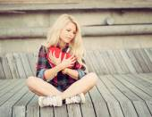 Sad lonely girl sitting on wood planks and hugging a big red heart — Stock Photo