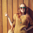 Beautiful redheaded girl with fashionable big bag in sunglasses standing near wooden wall — Stock Photo #54952381