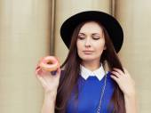 Beautiful brunette girl looking for a tasty pink donut — Stockfoto