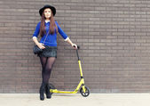 Beautiful brunette girl in a hat with a yellow scooter stands near the brick wall — Foto de Stock