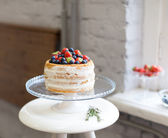 Beautiful biscuit cake with white cream decorated with strawberries and blueberries on a white pedestal stands at the window — Stock Photo