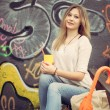 Beautiful young blonde woman sitting with a glass of yellow paper bag for lunch, with a multi-colored umbrella near graffiti wall. Outdoor — Stock Photo #57247869