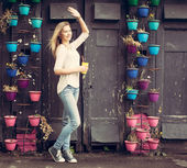Girl in jeans and sneakers with a yellow cup waving near the wall with flowers. Outdoor — Stock Photo