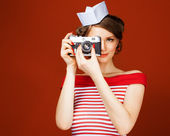 Beautiful pin-up girl holding a vintage camera and directs it straight to the camera. Red background, close up — Stock Photo