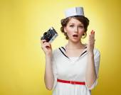 Beautiful pin-up girl dressed a sailor holding a vintage camera and screams behind his hand. Yellow background, close up — Stock Photo