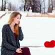 Beautiful fashionable girl sits in the winter on a bench next to a red heart in loneliness. Toned in warm colors. — Foto de Stock   #62972259