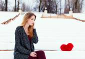 Beautiful fashionable girl sits in the winter on a bench next to a red heart in loneliness. Toned in warm colors. — Stock Photo