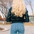 Pretty young fashion sexy girl with beautiful long blond hair on the road in evening summer time have fun and shows her nice back in jeans   — Stock Photo #70643675