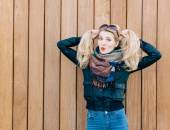 Beautiful blonde girl in black jacket posing nex to wooden wall on a sunny day and playing with her hair — Stock Photo