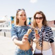 Young sexy blonde best friends girls eating ice cream in summer hot weather in sunglasses have fun and good mood looking in camera and smiling. Warm colors. — Stock Photo #80387340