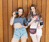 The best lifestyle portrait of two best friends girls wearing stylish bright outfits, denim shorts and vintage camera. On background wall of wooden planks — Stock Photo