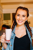 Beautiful girl with braids sitting in a cafe and drinking a milkshake, smiling at the camera — Stock Photo