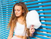 Beautiful young woman with dreads posing near blue plank wall with cotton candy summer warm evening — Stock Photo