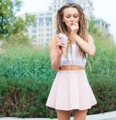 Young sexy blonde girl with dreads eating multicolored ice cream in waffle cones in summer evening,  joyful and cheerful.  European city center, at the park. — Stock Photo