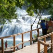 Tourists walking in front of the waterfalls of the Krka — Stock Photo #59432219