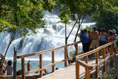 Tourists walking in front of the waterfalls of the Krka  — Stock Photo