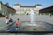 Childern plying with a ball on a fountain — Stock Photo