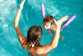 Adorable baby enjoying swimming in a pool with his mother — Stock Photo