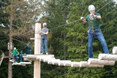 Visitors in adventure park clambering — Stock Photo