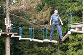 Visitors in adventure park clambering — Stock Photo