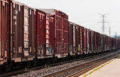 Red freight train box cars in perspective — Stock Photo